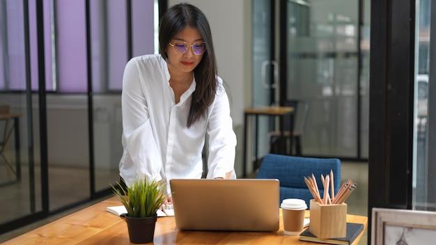 Portret pracownica stałego i pracy z laptopem i materiały biurowe w wygodnym pomieszczeniu biurowym