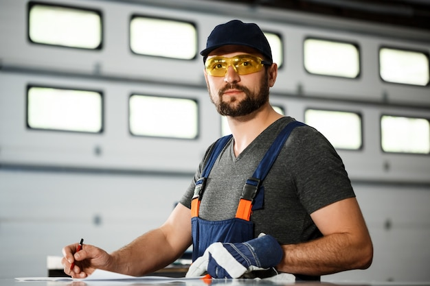 Portret pracownik w kombinezonach, stalowy fabryczny tło.