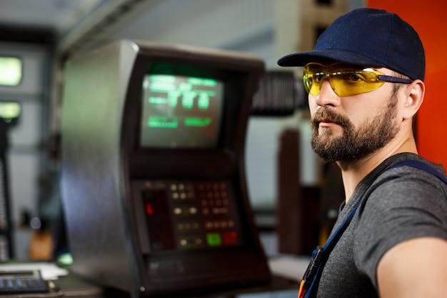 Portret pracownik w onalls zbliża komputer, stalowy fabryczny tło.