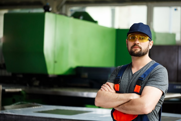 Portret pracownik z krzyżować rękami, stalowy fabryczny tło.