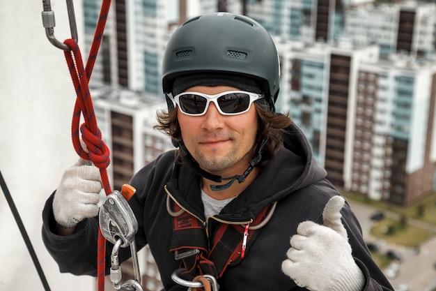 Portret pracownika alpinizmu przemysłowego w mundurze na dachu budynku mieszkalnego elewacji podczas pracy wysokościowej. robotnik linowy na dachu domu. koncepcja przemysłowych prac urbanistycznych. skopiuj miejsce