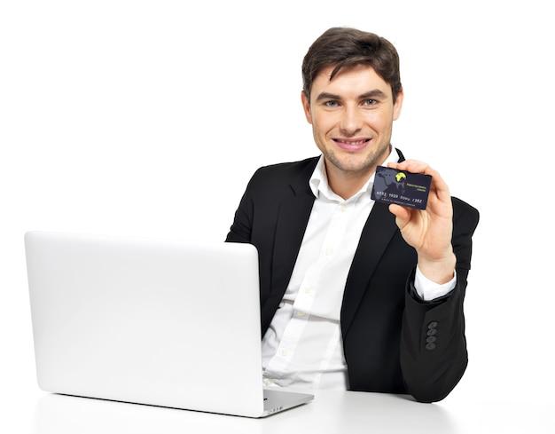 Portret pracownika biurowego z laptopa i karty kredytowej, siedząc na stole na białym tle.