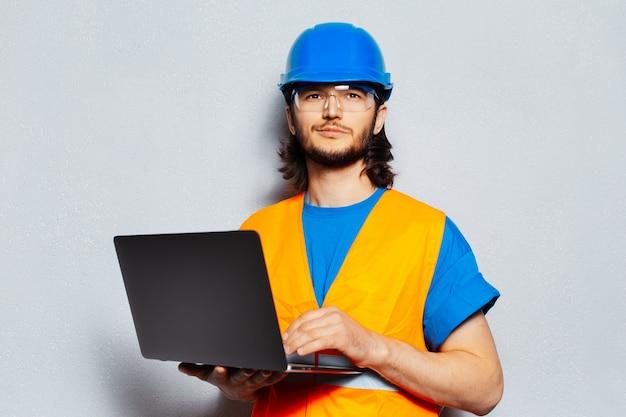 Portret pracownika budowlanego noszącego sprzęt bezpieczeństwa za pomocą laptopa na szarym tle