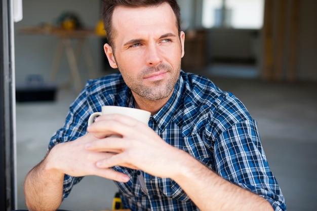 Portret pracownika budowlanego picia kawy na zewnątrz