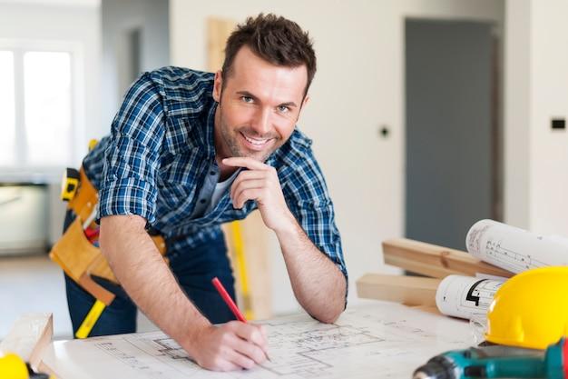 Portret pracownika budowlanego z planami