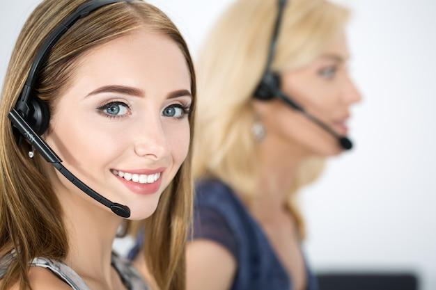 Portret pracownika call center w towarzystwie jej zespołu. uśmiechnięty operator obsługi klienta w pracy. koncepcja pomocy i wsparcia