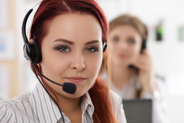 Portret pracownika call center w towarzystwie jej zespołu. uśmiechnięty operator obsługi klienta w pracy