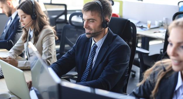 Portret pracownika call center w towarzystwie swojego zespołu. uśmiechnięty operator obsługi klienta w pracy.