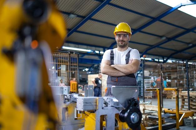 Portret pracownika fabryki stojący przy maszynie przemysłowej