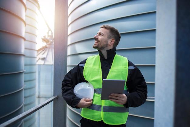 Portret pracownika fabryki z komputerem typu tablet stojący na metalowej platformie między przemysłowymi zbiornikami magazynowymi i patrzący w bok.