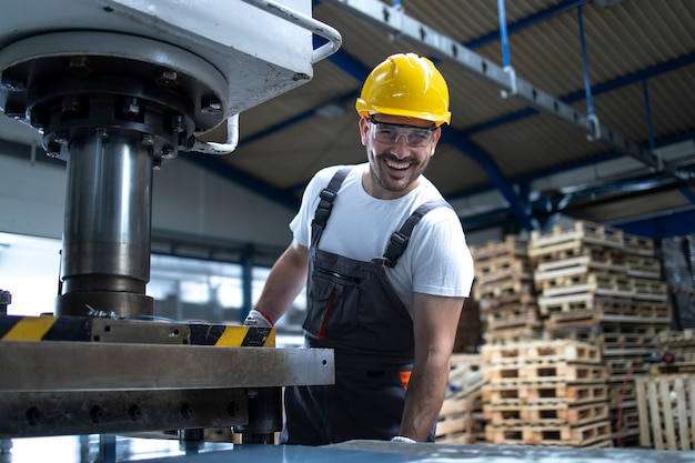 Portret pracownika fabryki z rękami skrzyżowanymi stojący przy wiertarce w zakładzie przemysłowym