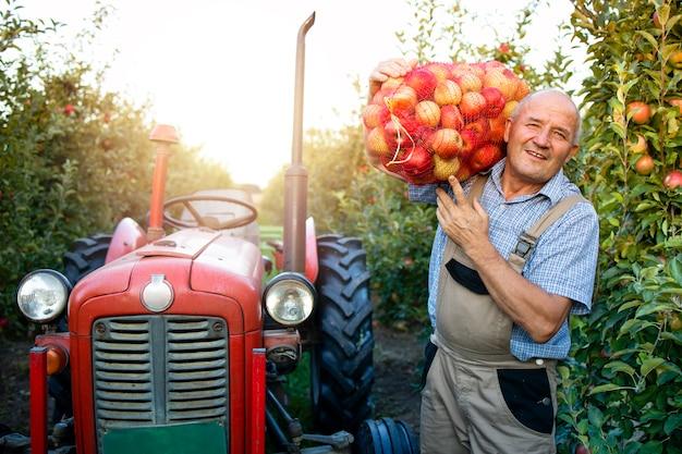 Portret pracownika gospodarstwa worek pełen owoców jabłka obok starej maszyny ciągnika w stylu retro.