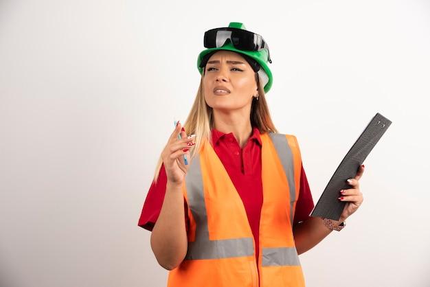 Portret pracownika kobieta przemysł noszenie mundur bezpieczeństwa i okulary stojąc na białym tle.