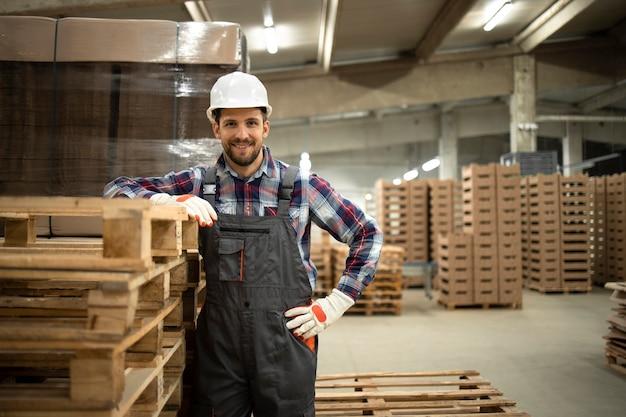 Portret pracownika magazynu stojącego przez drewnianą paletę w fabrycznym magazynie.