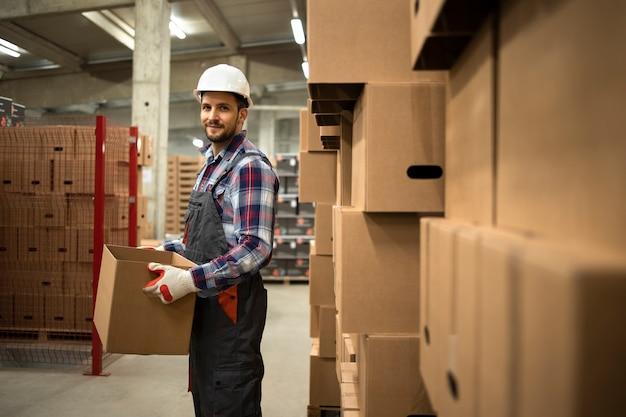 Portret pracownika magazynu w ubraniu roboczym i kasku ochronnym trzymającego karton przenoszący towary w magazynie fabrycznym.