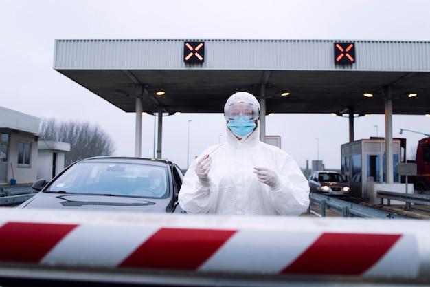 Portret pracownika medycznej opieki zdrowotnej w białym kombinezonie ochronnym, w rękawiczkach, stojącego na punkcie kontrolnym i trzymającego zestaw testowy na covid-19.