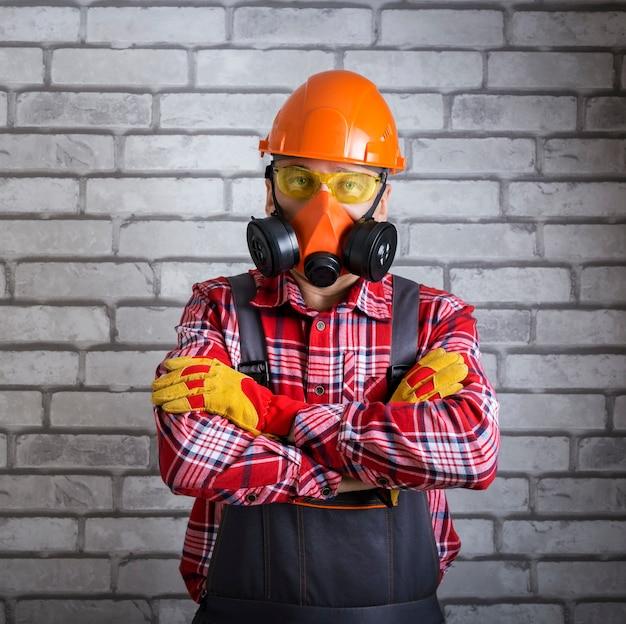 Portret pracownika noszącego sprzęt ochronny. konstruktor ze sprzętem zabezpieczającym przed powierzchnią ściany z cegły.