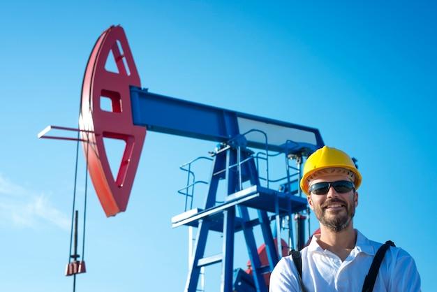 Portret pracownika pola naftowego stojącego przy platformie