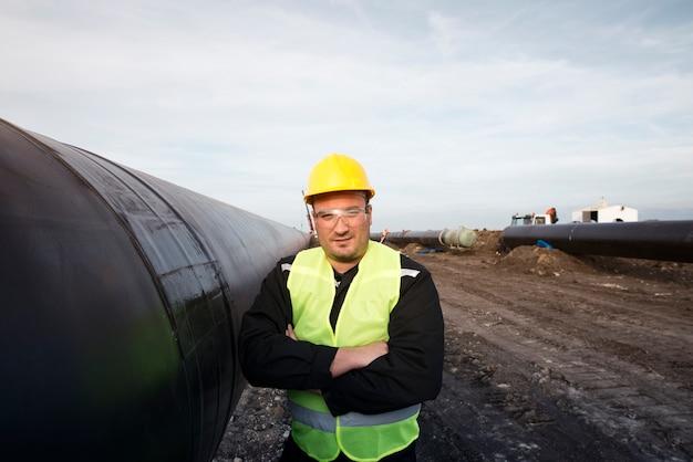 Portret pracownika pola naftowego stojącego przy rurze gazowej na budowie