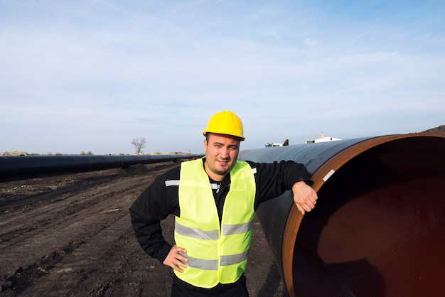 Portret pracownika przemysłowego stojącego przy rurze gazowej na budowie