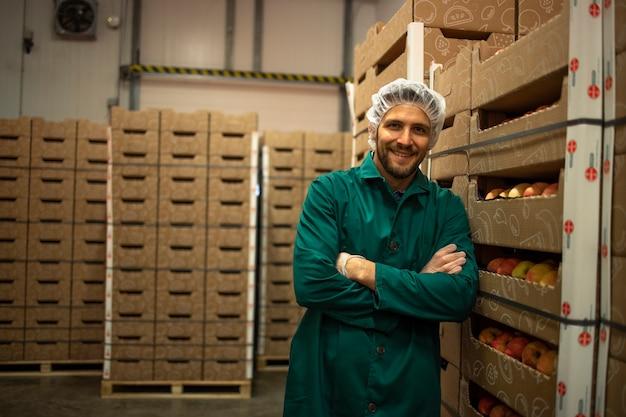 Portret pracownika stojącego przy skrzyniach jabłek w magazynie fabryki żywności ekologicznej.