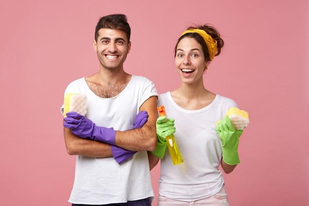Portret pracowników usług sprzątających w ochronnych rękawicach gumowych, trzymających szmaty i detergent