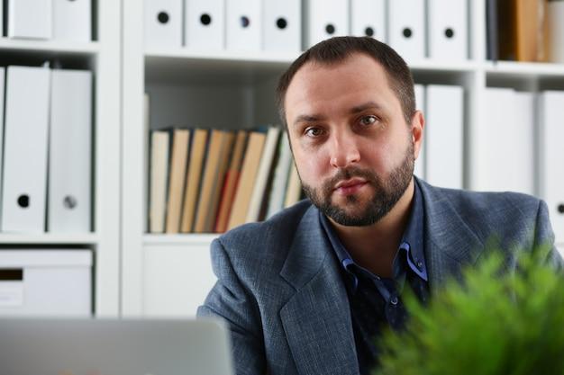 Portret pracującego mężczyzny siedzącego przy stole z laptopem