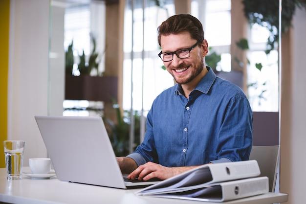 Portret pracuje na laptopie przy kreatywnie biurem rozochocony biznesmen
