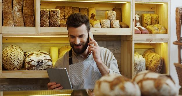 Portret pracuje w piekarnia sklepie szczęśliwy piekarz używa cyfrowego pastylka komputer i opowiadający na telefonie komórkowym