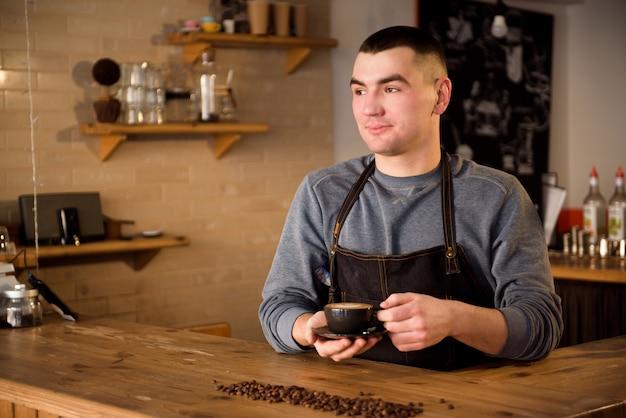 Portret profesjonalisty barista mężczyzna w fartuchu trzyma filiżankę gorąca kawa przy kawiarnią