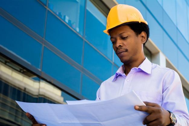 Portret profesjonalnego architekta w kasku patrząc na niebieskie wydruki na zewnątrz nowoczesnego budynku. koncepcja inżyniera i architekta.