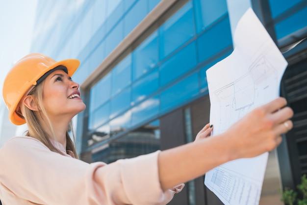 Portret profesjonalnego architekta w żółtym kasku i patrząc na niebieskie wydruki na zewnątrz nowoczesnego budynku. koncepcja inżyniera i architekta.