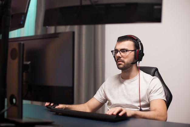 Portret profesjonalnego gracza grającego w strzelanki na potężnym komputerze z wieloma monitorami.