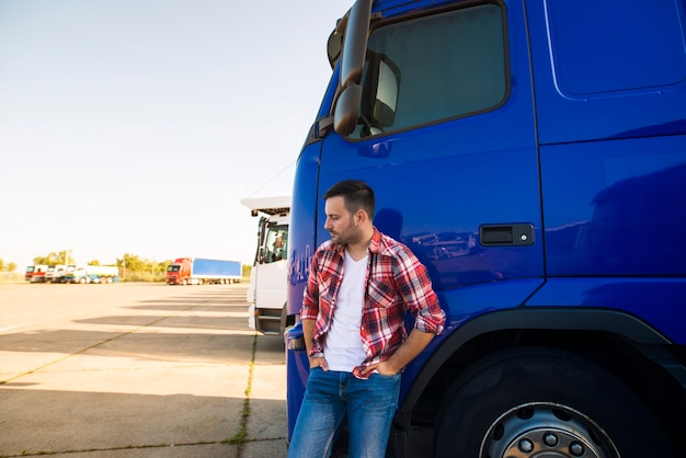 Portret profesjonalnego kierowcy ciężarówki stojącego przy jego pojeździe ciężarówki