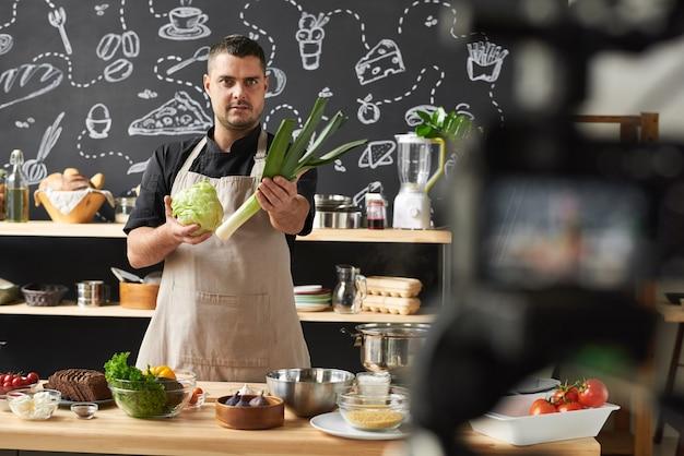 Portret profesjonalnego kucharza trzymającego świeże warzywa i opowiadającego o nich do kamery na swoim blogu