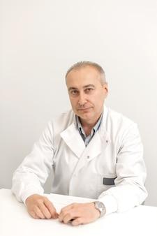 Portret profesjonalnego lekarza płci męskiej w białym fartuchu, siedząc przy stole