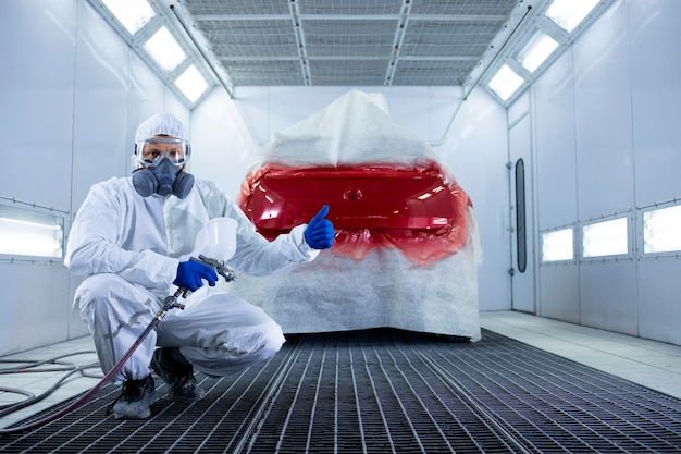 Portret profesjonalnego malarza samochodowego w ubraniu ochronnym i masce trzymającego kciuki do góry i stojącego przy samochodzie w komorze malarskiej.