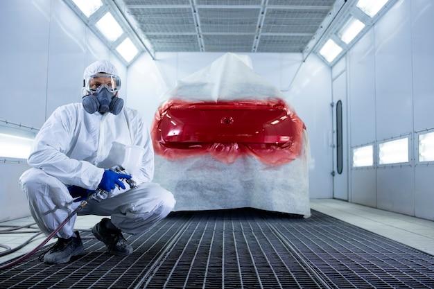 Portret profesjonalnego malarza samochodowego w ubraniu ochronnym i masce, trzymającego pistolet malarski i stojącego przy samochodzie w komorze.