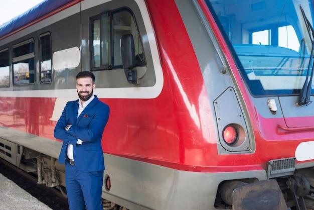 Portret profesjonalnego maszynisty stojącego przy szybkim pociągu na stacji