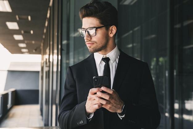 Portret profesjonalnego młodego biznesmena ubranego w formalny garnitur stojący na zewnątrz budynku ze szkła i trzymając smartfon