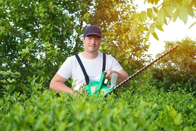 Portret profesjonalnego ogrodnika gospodarstwa trymer do pracy na podwórku