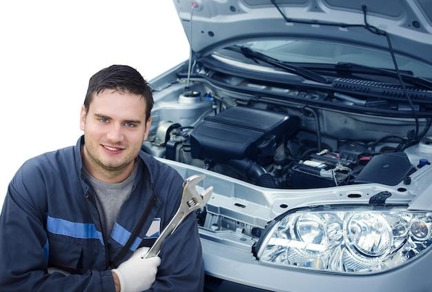 Portret profesjonalnego przystojnego mechanika samochodowego trzymającego klucze przed samochodem z otwartą maską.