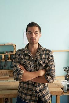 Portret profesjonalnego stolarza stojącego w ramiona warsztatowe złożone