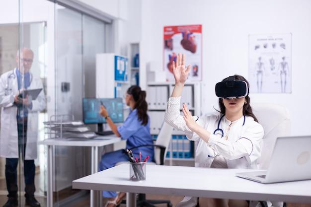 Portret profesjonalnej lekarki w okularach vr, siedzącej w prywatnej szafce szpitalnej i wykonującej gesty za pomocą innowacji wirtualnej rzeczywistości, podczas gdy zespół lekarzy pracuje na tle