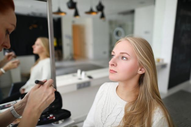 Portret profesjonalnej wizażystki nakładającej szminkę za pomocą specjalnego sprzętu. młoda piękna kobieta w gabinecie kosmetycznym. specjalistyczna rudowłosa specjalistyczna paleta z cieniami do powiek. koncepcja mua