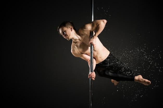 Portret profesjonalny model mężczyzna wykonuje taniec na rurze