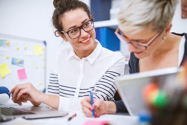 Portret profesjonalnych kobiet w średnim wieku pracujących razem nad projektami w biurze.