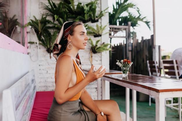 Portret profil atrakcyjna ładna dziewczyna w letnie ubrania siedzi w stylowej restauracji na świeżym powietrzu z kawą z egzotycznymi roślinami