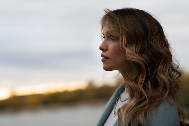 Portret profil atrakcyjnej młodej kobiety na zewnątrz