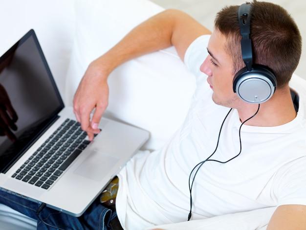 Portret profil młody facet słuchanie muzyki w słuchawkach z laptopa w domu